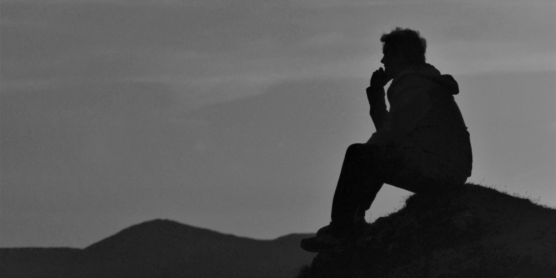 a man sitting on a hill and thinking